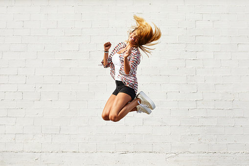 Happy young woman jumping mid-air in front of white wall - gettyimageskorea