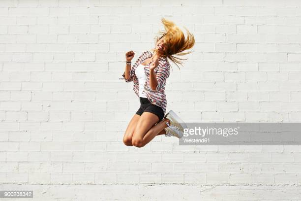 happy young woman jumping mid-air in front of white wall - festeggiamento foto e immagini stock
