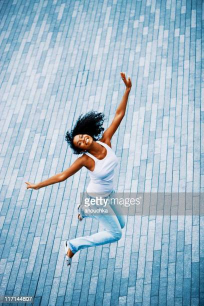 Happy Young Woman Jumping on the street