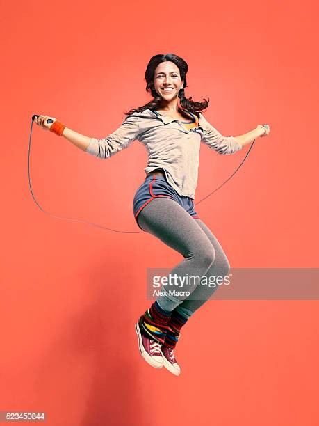 happy young woman jumping with skipping rope - orange background stock pictures, royalty-free photos & images