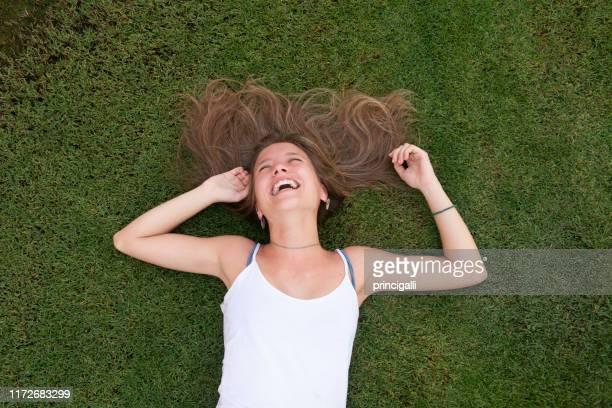 jeune femme heureux s'étendant sur l'herbe - bras humain photos et images de collection