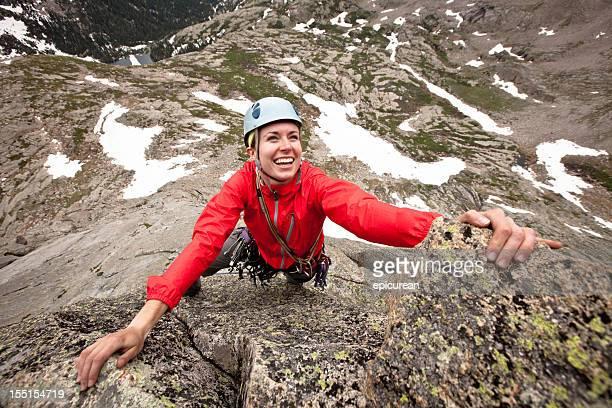 Glückliche junge Frau, die eine Kletter-route in Colorado