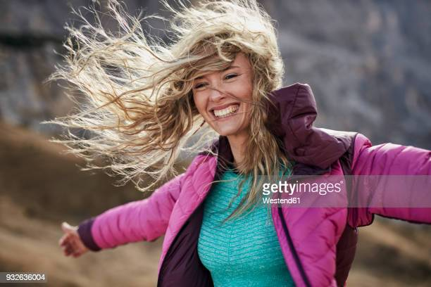 happy young woman leaning against the wind in the mountains - wind stock pictures, royalty-free photos & images
