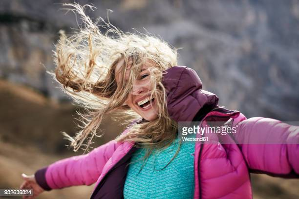 happy young woman leaning against the wind in the mountains - windzerzaustes haar stock-fotos und bilder