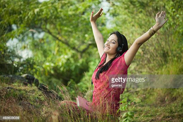 Happy young woman listening music in nature.