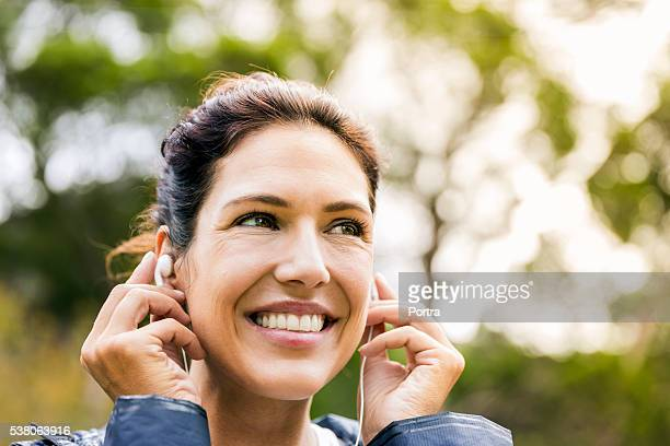 Glückliche junge Frau anhören Musik im Freien