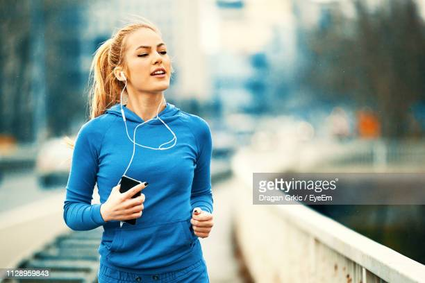 happy young woman listening music while jogging on bridge - joggeuse photos et images de collection