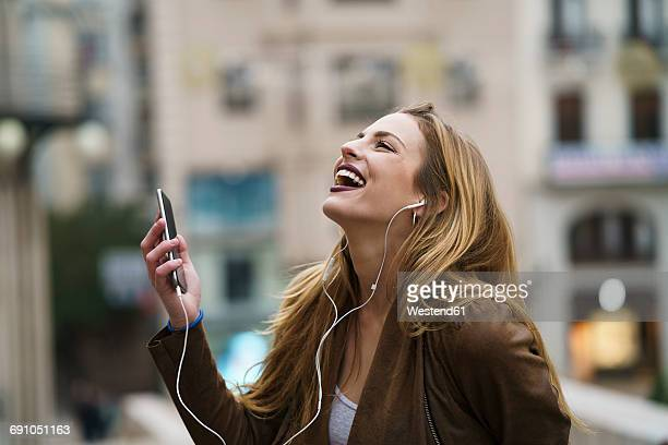Happy young woman listening music with earphones and smartphone