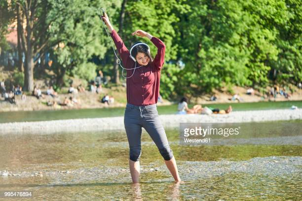 happy young woman listening music with headphones and cell phone dancing at riverside - fiume isar foto e immagini stock
