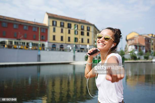 Happy young woman listening to music at the riverside