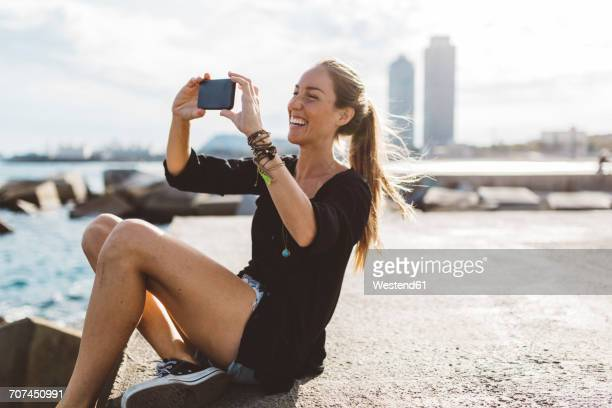 happy young woman looking at cell phone at the seafront - capturing an image stock pictures, royalty-free photos & images