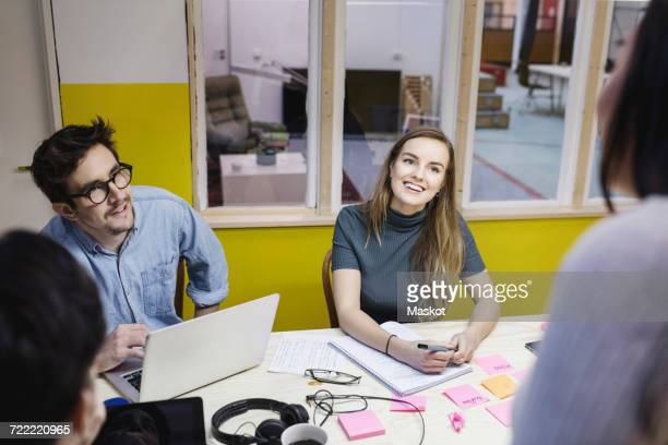 Happy young woman looking at colleague during meeting in creative office