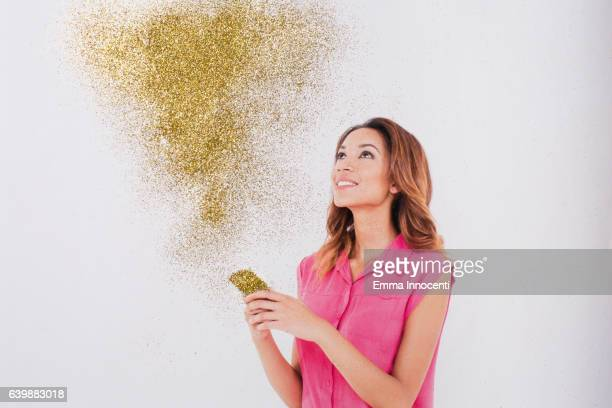 Happy young woman looking at gold dust coming from phone