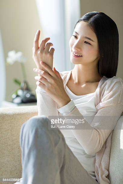 Happy young woman looking at her fingernails