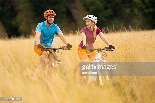 Happy Young Woman Looking At Man Both Cycling On Electric