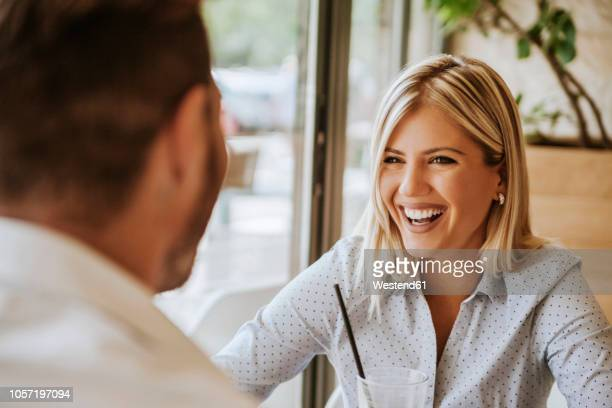 happy young woman looking at man in a cafe - dating stock-fotos und bilder
