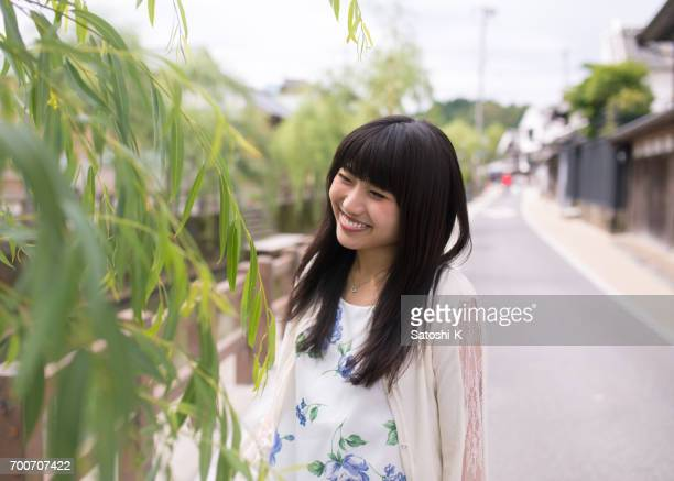 Happy young woman looking at willow tree on street