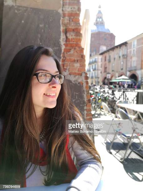 happy young woman looking away while sitting at sidewalk cafe - イタリア パヴィア ストックフォトと画像