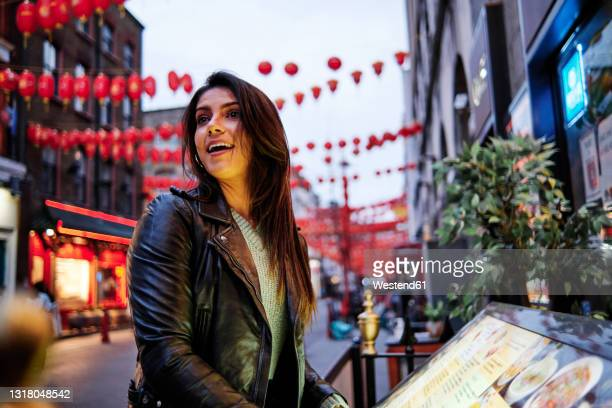 happy young woman looking away while standing in city - embellished jacket stock pictures, royalty-free photos & images