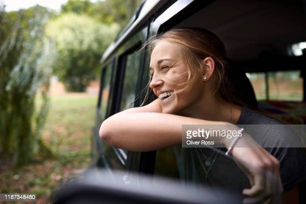 happy young woman looking out of car window - junge frau allein stock-fotos und bilder