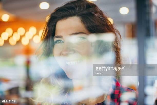 gelukkig jonge vrouw op zoek venster bekijken door glas - achter stockfoto's en -beelden