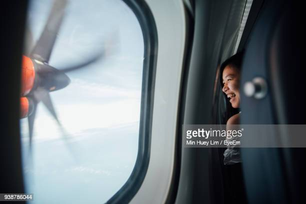 Happy Young Woman Looking Through Window In Airplane