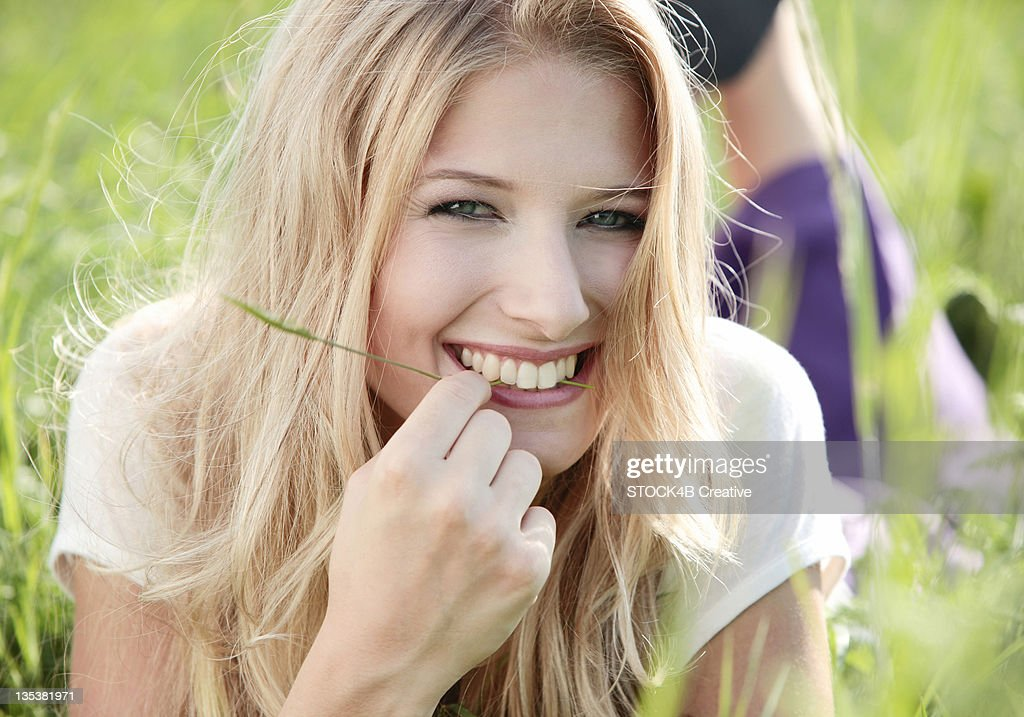 Happy young woman lying in meadow : Stock Photo