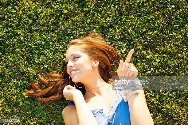 Heureuse Jeune femme allongée sur l'herbe et à l'écoute de la musique.