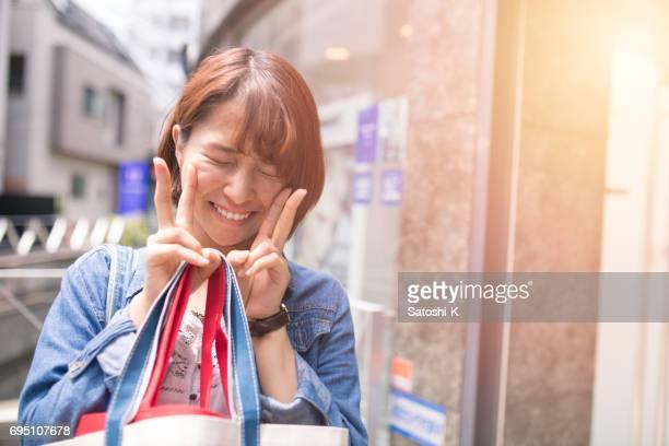 恥ずかしがり屋のピースサインを作って幸せな若い女