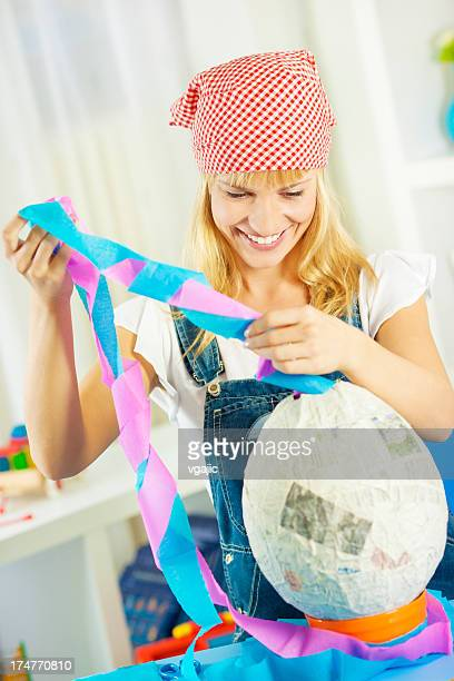 Happy Young Woman Making Pinata