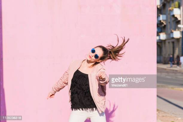 happy young woman moving in front of pink wall - city life stock-fotos und bilder