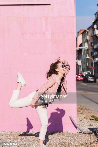 happy young woman moving in front of pink wall - standing on one leg stock pictures, royalty-free photos & images