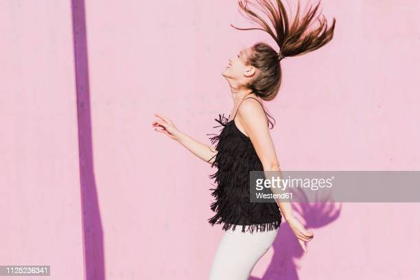happy young woman moving in front of pink wall - à franges photos et images de collection