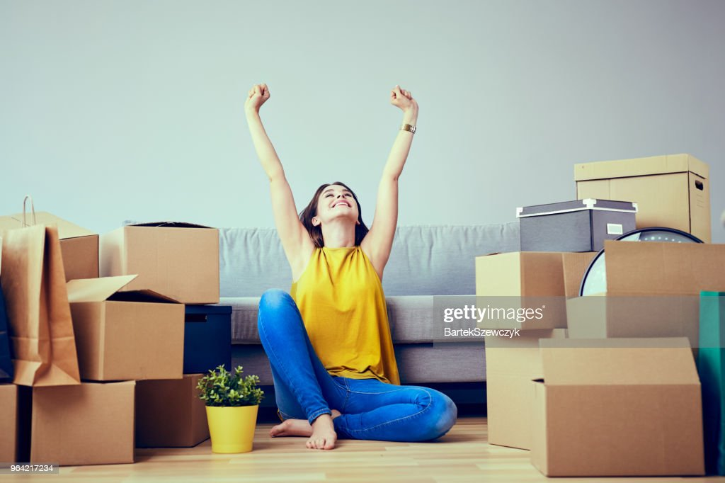 Happy young woman moving to new home - having fun : Stock Photo