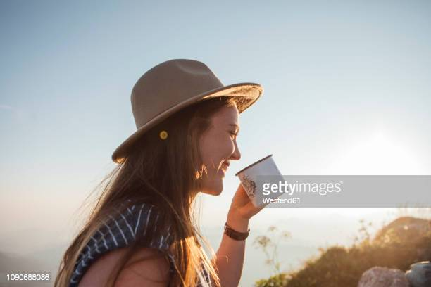happy young woman on a hiking trip at sunrise holding a cup - morning stock pictures, royalty-free photos & images