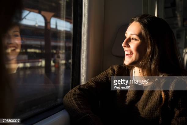 Happy young woman on a train looking out of window