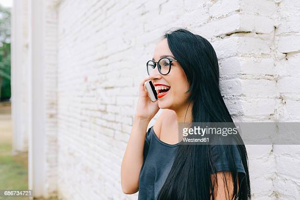 Happy young woman on cell phone in front of brick wall