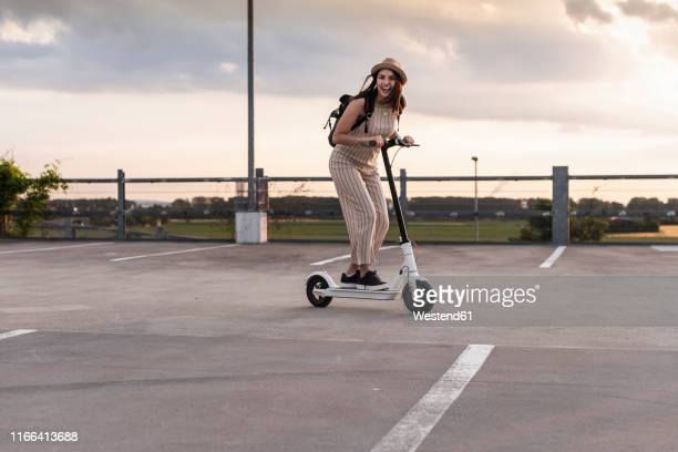 happy young woman on electric scooter on parking deck - electric scooter stock pictures, royalty-free photos & images