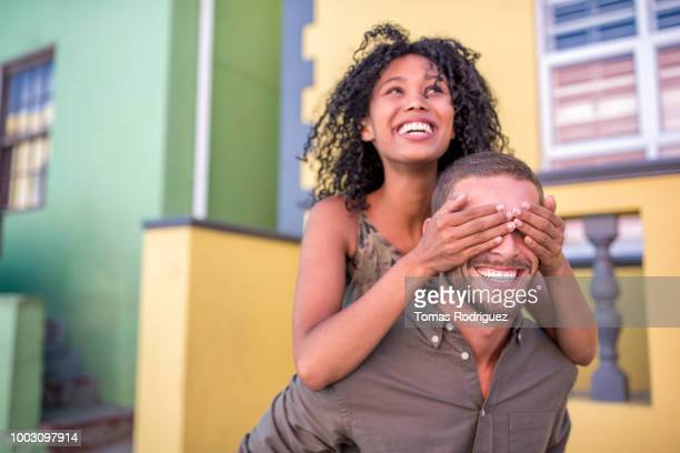 Happy young woman on man's back covering his eyes