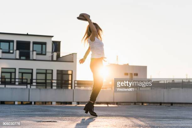 happy young woman on parking level in the city at sunset - city life stock-fotos und bilder