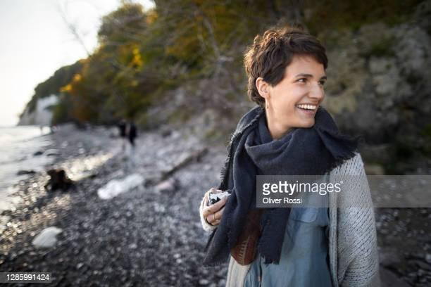 happy young woman on the beach turning round - mensch im hintergrund stock-fotos und bilder