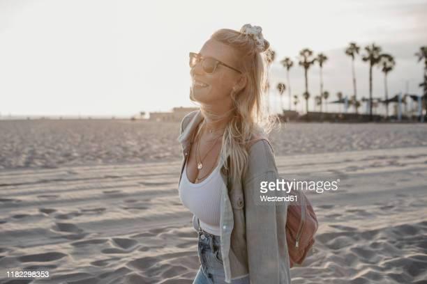happy young woman on the beach, venice beach, california, usa - サンタモニカ ストックフォトと画像