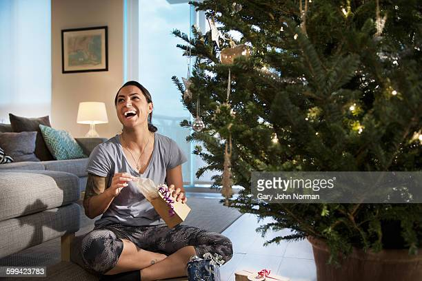 Happy young woman opening a gift.