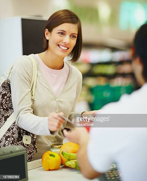 Happy young woman paying for goods at the cash counter