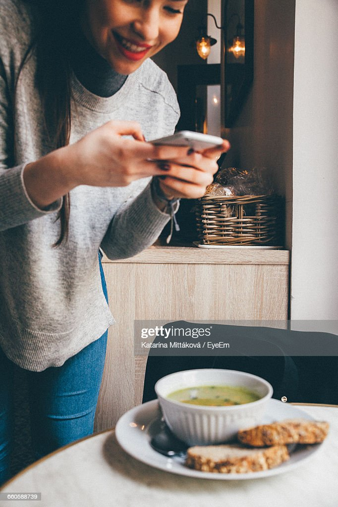 Happy Young Woman Photographing Food On Table : Stock Photo