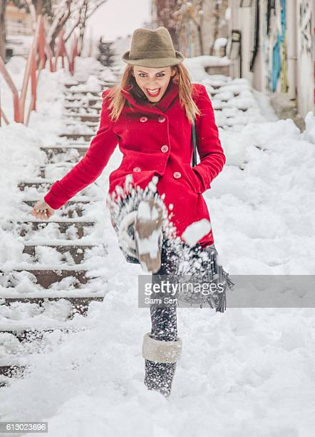 Happy young woman play with snow in winter time