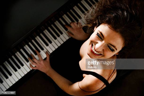 Happy Young Woman Playing Piano