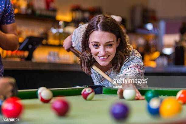 Happy Young Woman Playing Pool in a Bar