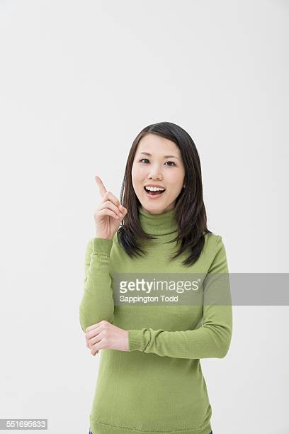happy young woman pointing at something - gesturing stock pictures, royalty-free photos & images