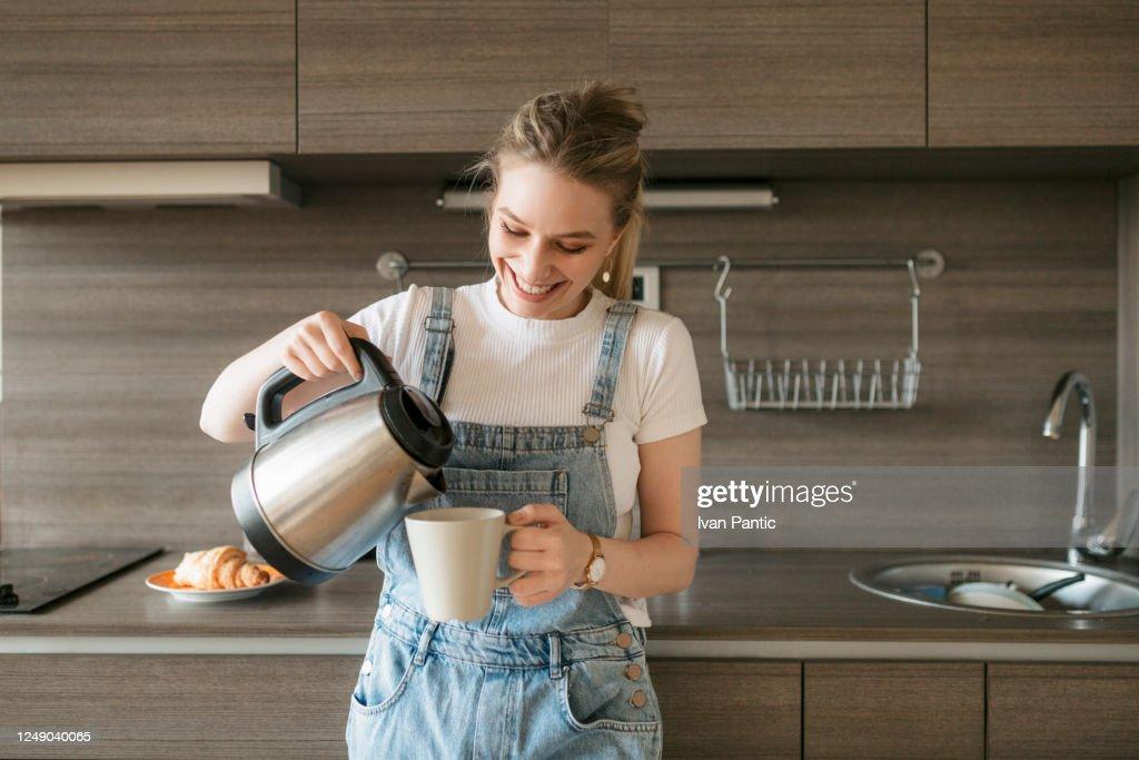 Gelukkige jonge vrouw die zich sommige ochtendkoffie giet : Stockfoto